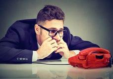 Отчаянный бизнесмен ждать кто-то для того чтобы вызвать его стоковое изображение rf