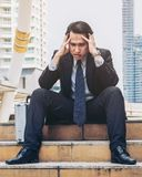 Отчаянный бизнесмен сидя безвыходно на поле лестницы стоковая фотография