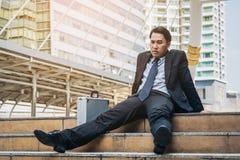 Отчаянный бизнесмен сидя безвыходно на поле лестницы стоковое изображение