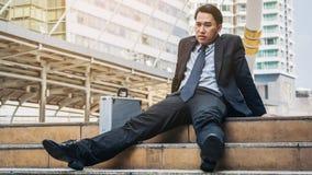 Отчаянный бизнесмен сидя безвыходно на поле лестницы стоковые фото