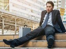 Отчаянный бизнесмен сидя безвыходно на поле лестницы стоковая фотография rf