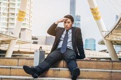 Отчаянный бизнесмен сидя безвыходно на поле лестницы стоковое фото