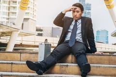 Отчаянный бизнесмен сидя безвыходно на поле лестницы стоковое фото rf