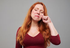 Отчаянный и унылый плакать молодой женщины изолированный над серым цветом Стоковое Изображение