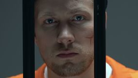 Отчаянный пленник со шрамами на стороне смотря через бары клетки, лишении свободы акции видеоматериалы