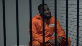 Отчаянный черный пленник сидя в клетке, неправильно обвиненный человек, небезупречная система сток-видео