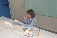 Отчеты об успешной азиатской коммерсантки читая финансовые и чувствовать счастливый стоковое фото