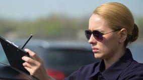Отчет о дорожного происшествия дамы полиции подписывая около патрульной машины, пишет вне паркуя штраф сток-видео