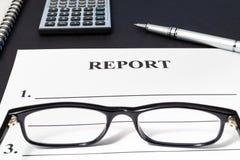 Отчет с ручкой, стеклами и калькулятором на черной таблице стоковая фотография rf