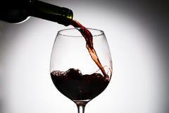 От бутылки вина зеленого стекла лить в стекло Стоковое Изображение