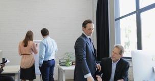 Отделка бизнесмена работая с компьютером приносит отчет к его коллеге, команду группы предпринимателей современную работая внутри акции видеоматериалы