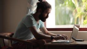 Отделка молодого человека работая на компьтер-книжке и полагается назад на стуле видеоматериал