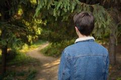 От заднего мальчика подростка в лесе стоковая фотография