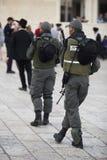 От задних 2 людей в форме и с оружиями и людьми стойте Стоковые Изображения