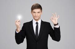 Отличная идея! Бизнесмен Hansome молодой держа электрическую лампочку  Стоковое Изображение RF