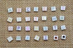 От начала до конца английский алфавит на предпосылке мешковины Стоковая Фотография