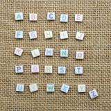 От начала до конца английский алфавит на предпосылке мешковины Стоковое Фото
