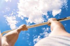От первого лица взгляд турника Тяги парня вверх на баре Разминка Outdoors Голубое небо на blackground Стоковое Фото