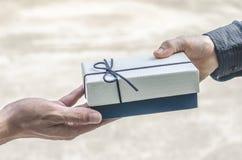 От рук к рукам Конец-вверх рук держа подарочную коробку давая a Стоковое Фото