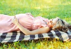 Отдыхать беременной женщины лежа на траве в лете Стоковое Фото