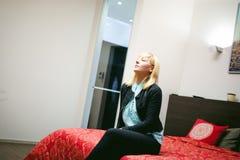 Отдыхать белокурой женщины сидя на кресле в живущей комнате дома Стоковая Фотография RF