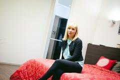 Отдыхать белокурой женщины сидя на кресле в живущей комнате дома Стоковые Изображения RF