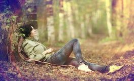 Отдыхать девушки туристский в лесе Стоковые Фотографии RF