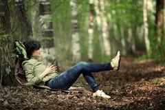 Отдыхать девушки туристский в лесе Стоковая Фотография RF