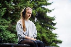 Отдыхать жизнерадостной атлетической женщины сидя после тренировки в парке на стенде с телефоном и наушниками Стоковая Фотография