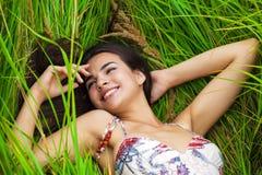 Отдыхать и день молодой женщины лежа вниз на зеленой траве Стоковое Изображение