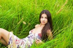 Отдыхать и день молодой женщины лежа вниз на зеленой траве Стоковые Изображения RF