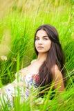 Отдыхать и день молодой женщины лежа вниз на зеленой траве Стоковые Фотографии RF