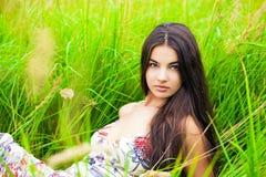 Отдыхать и день молодой женщины лежа вниз на зеленой траве Стоковое Фото
