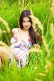 Отдыхать и день молодой женщины лежа вниз на зеленой траве Стоковая Фотография