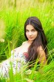 Отдыхать и день молодой женщины лежа вниз на зеленой траве Стоковые Изображения