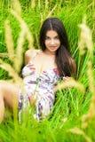 Отдыхать и день молодой женщины лежа вниз на зеленой траве Стоковая Фотография RF