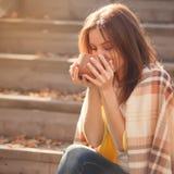Отдыхать молодой женщины и выпивая чай сидя в саде осени на шагах, обернутых в шерстяном одеяле шотландки Стоковое Изображение