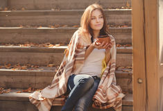 Отдыхать молодой женщины и выпивая чай сидя в саде осени на шагах, обернутых в шерстяном одеяле шотландки Стоковые Изображения