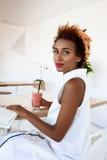 Отдыхать smoothie молодой красивой африканской девушки выпивая усмехаясь в кафе Стоковое Изображение RF