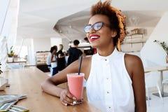 Отдыхать smoothie молодой красивой африканской девушки выпивая усмехаясь в кафе Стоковые Изображения