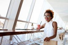 Отдыхать smoothie молодой красивой африканской девушки выпивая усмехаясь в кафе Стоковая Фотография RF