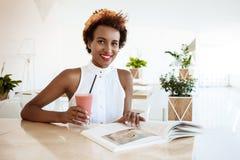 Отдыхать smoothie молодой красивой африканской девушки выпивая усмехаясь в кафе Стоковые Изображения RF