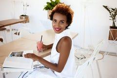 Отдыхать smoothie молодой красивой африканской девушки выпивая усмехаясь в кафе Стоковая Фотография