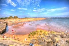 Отдыхающие наслаждаясь тепловой волной в пляже Девоне Dawlish Уоррена на летний день в 2013 стоковые изображения rf
