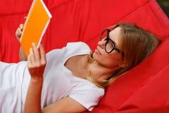 Отдыхая лежать в книге чтения гамака Стоковое фото RF