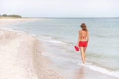 Отдыхая женщина идущ и наслаждающся на пляже Стоковые Изображения