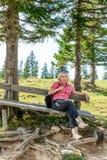Отдыхая женщина на деревянной скамье стоковые изображения rf