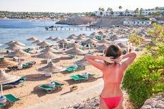 Отдыхая женщина стоящ и наслаждающся внутри на пляже стоковое фото