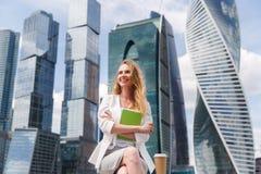 Офисные здания aganst молодой милой женщины сидя стоковые изображения