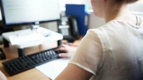 Офис: бизнес-леди печатая на ее компьютере сток-видео